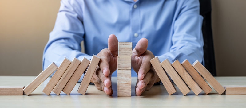 Businessman Hand Stopping Falling Wooden Blocks Or Dominoes. Bus