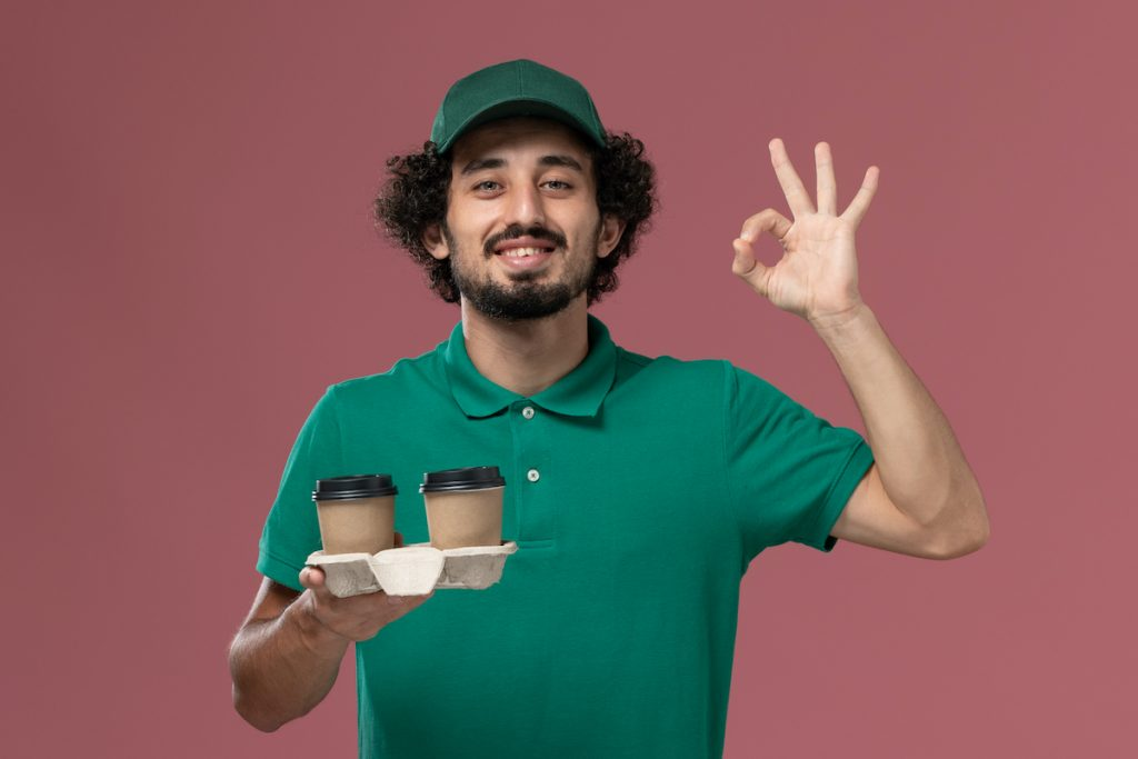Front View Male Courier In Green Uniform And Cape Holding Coffee Cups On Pink Background Service Uniform Delivery Job Male