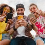 Happy Young Company Of Smiling Friends Sitting Park Using Smartphones, Man And Women Having Fun Together, Colorful Summer Hipster Fashion Style, Communication Wireless Connecting Devices