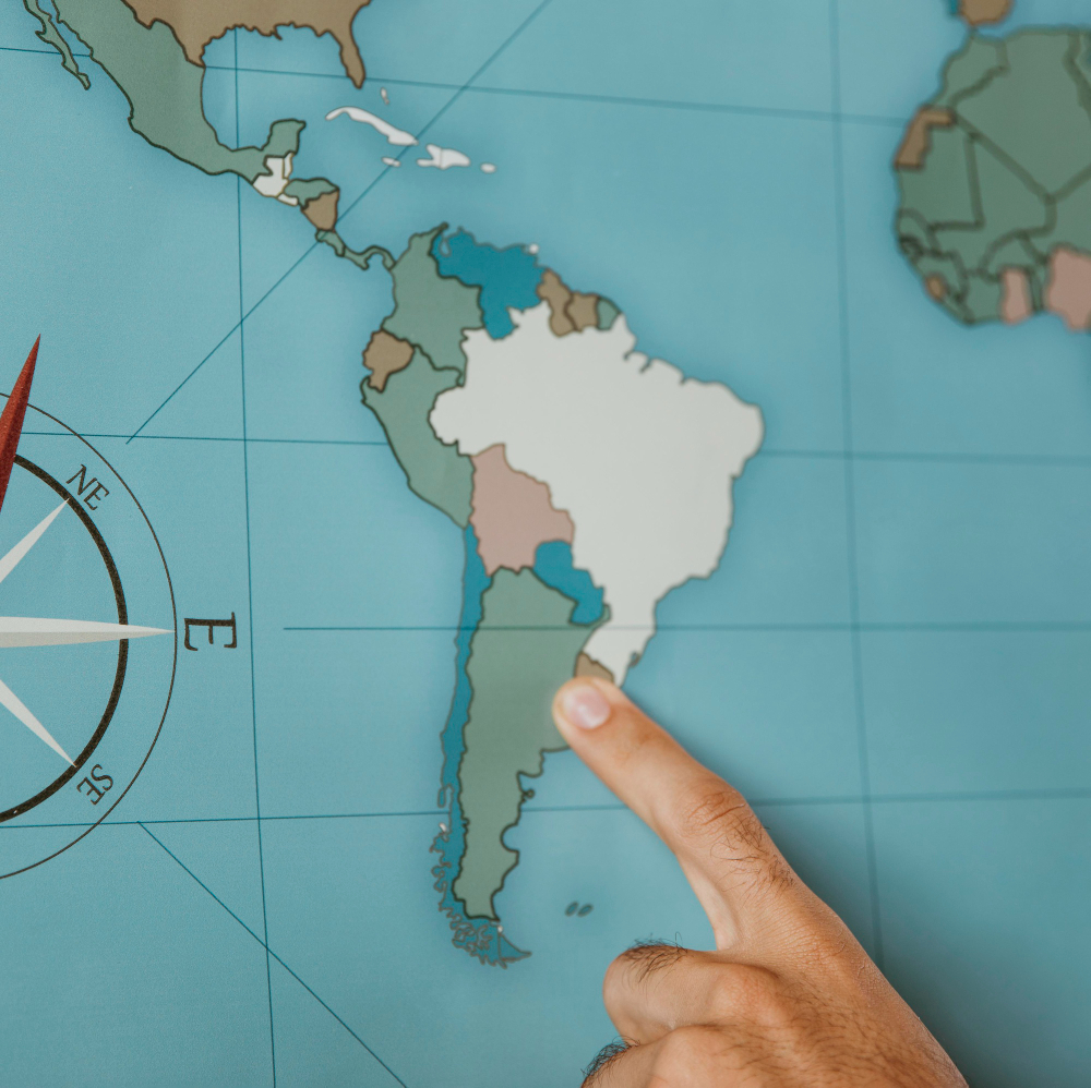 Person Pointing To South America On The Map